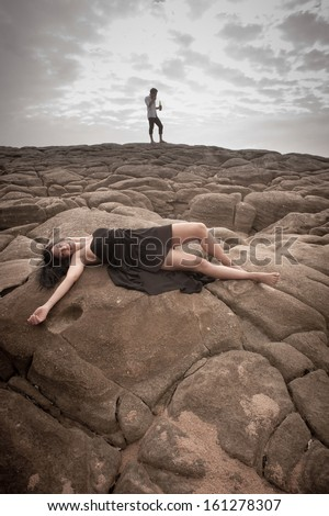 Young attractive caucasian woman lying on rocks with clouds overhead and man in background - stock photo