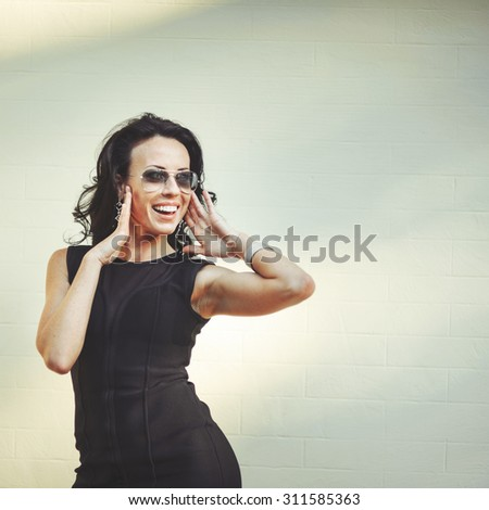 Young attractive cheerful brunette woman posing outside.  - stock photo