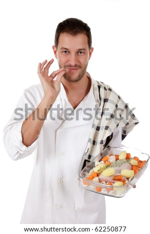 Young attractive chef caucasian male with uniform showing a tasty tenderloin piece with fresh vegetables and herbs in glassware. Studio shot. White background. - stock photo