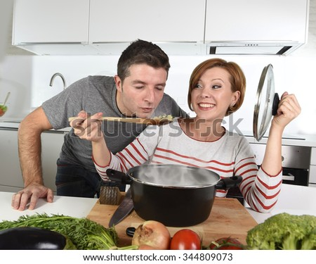 young attractive couple at home kitchen with husband or boyfriend tasting delicious vegetable stew cooked by her wife or girlfriend smiling happy in healthy eating and successful cooking concept - stock photo
