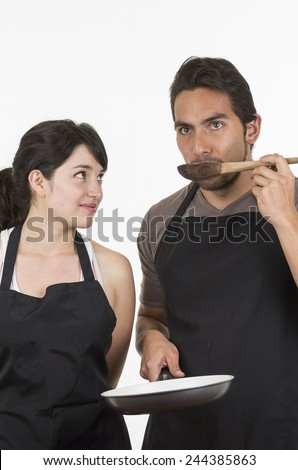young attractive couple chefs wearing black apron tasting food isolated on white - stock photo