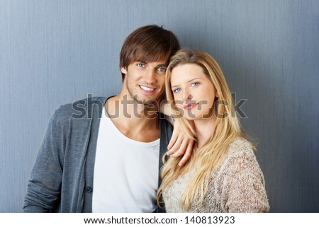 young attractive couple in front of grey wall - stock photo