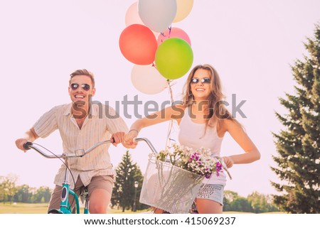 Young attractive couple in glasses riding bikes with balloons - stock photo