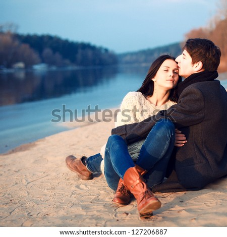 Young attractive couple in love posing in cold spring on the beach - stock photo