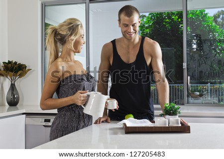 Young attractive couple in modern kitchen - stock photo