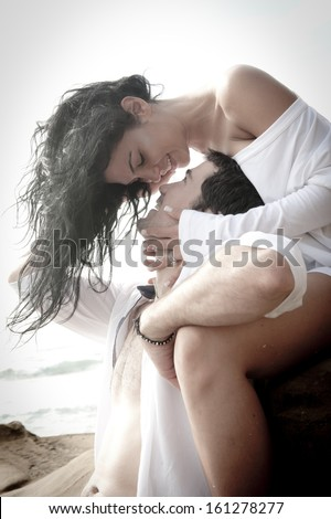 Young attractive couple kiss on rocks beach wearing white kissing love passionate - stock photo