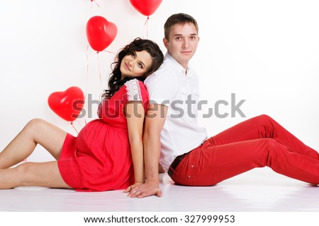 Young attractive couple: pregnant girl and her boyfriend are wearing red fashion clothes with red heart shape balloons isolated on white in studio - stock photo