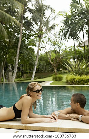 Young attractive couple relaxing by a swimming pool in a tropical garden. - stock photo