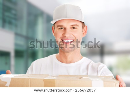 Young attractive courier guy delivering brown box - stock photo