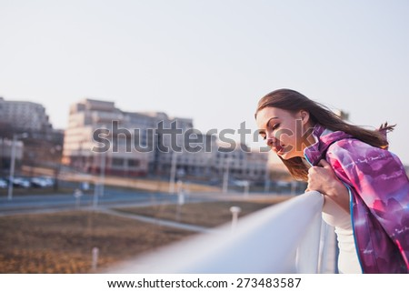 Young attractive curious girl in windbreaker looking at something behind the scene. Standing lean on railing. Urban scenery. Copy space. Vintage coloring - stock photo