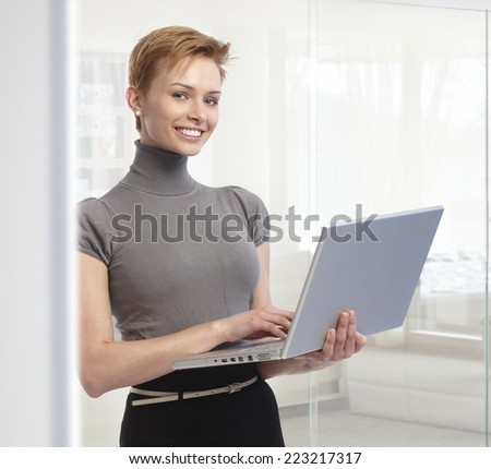Young attractive elegant caucasian businesswoman standing with laptop computer at office. Working, looking at camera, toothy smile.  . - stock photo