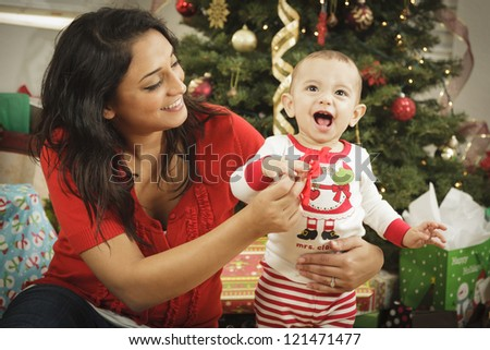Young Attractive Ethnic Woman With Her Newborn Baby Near The Christmas Tree. - stock photo