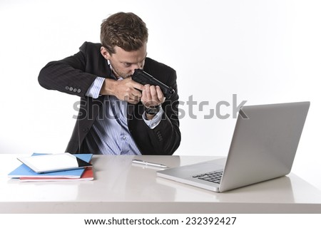 young attractive European businessman working in stress at office desk computer pointing gun to laptop in stress at work and overtime concept isolated on white background - stock photo