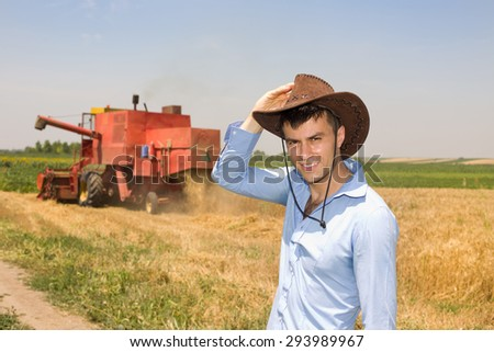 Young attractive farmer with cowboy hat standing in the field, combine harvester in background - stock photo