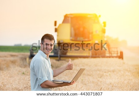Young attractive farmer with laptop standing in wheat field with combine harvester in background - stock photo