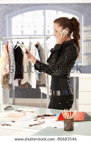 Young attractive fashion designer talking on phone by desk in office, working. - stock photo
