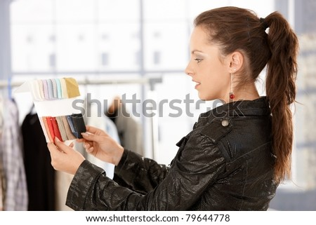 Young attractive fashion designer working in bright office, looking at colour scale.? - stock photo