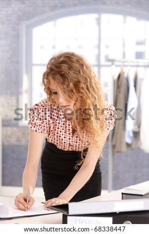 Young attractive fashion designer working in office at desk. - stock photo
