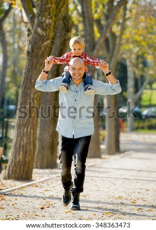 young attractive father carrying his happy little son on his shoulder walking together having fun on the park in Autumn sunny day smiling happy in family love and childhood concept - stock photo