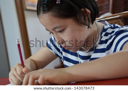 Young attractive female Asian student sitting at her desk and writing - stock photo