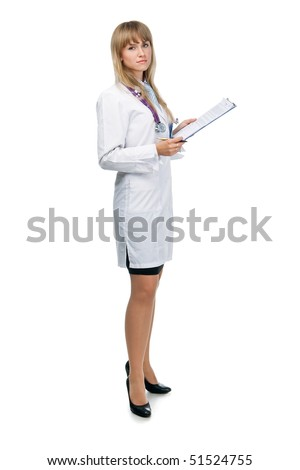 young attractive female doctor is standing with the clipboard and looking in the camera - stock photo