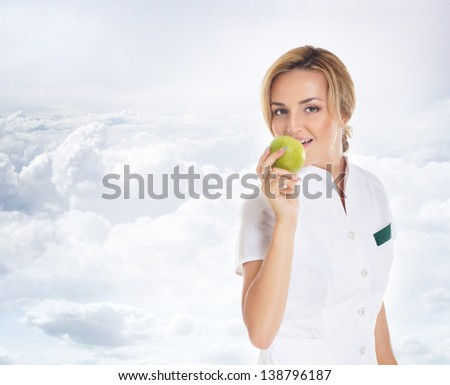 Young attractive female doctor isolated over the sky background - stock photo