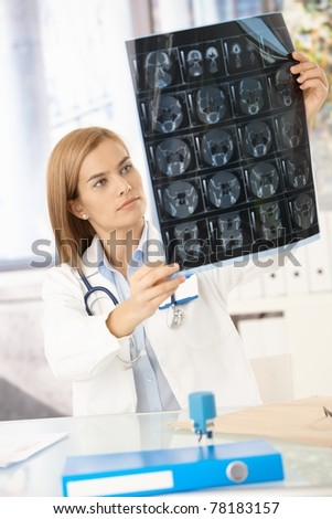 Young attractive female doctor sitting at desk, studying x-ray image.? - stock photo