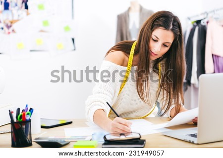 Young attractive female fashion designer leaning on office desk, working with a laptop at home - stock photo