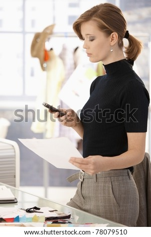 Young attractive female fashion designer standing at office desk, using mobile phone.? - stock photo