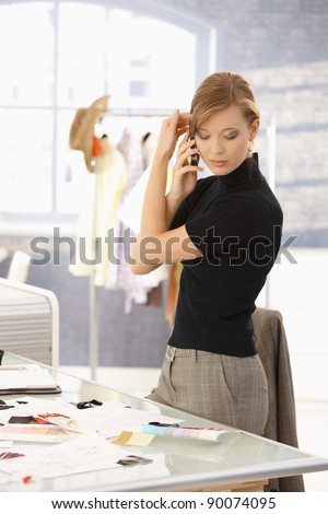 Young attractive female fashion designer talking on mobile phone in office, looking at patterns on desk.? - stock photo