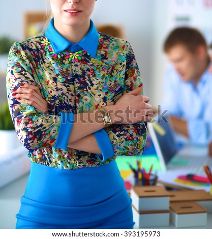 Young attractive female fashion designer working at office desk - stock photo