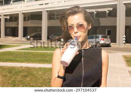Young attractive female fashion mode wearing fashionable dress drinking dietary cold fruit smoothie milk shake in the city while the weather is too hot - stock photo