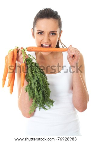 young attractive female holds bunch of carrots and try to eat one of them, isolated on white - stock photo