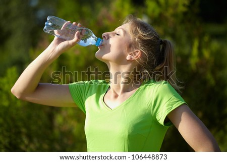 Young attractive female runner holds blue bottle of water - stock photo