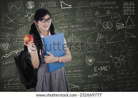 Young attractive female student standing at class while holding a red apple and folder - stock photo