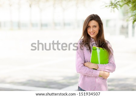 Young attractive female student with notebooks in her hands - stock photo