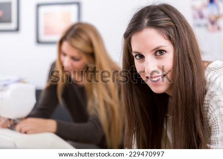 Young attractive females fashion designers leaning on office desk - stock photo