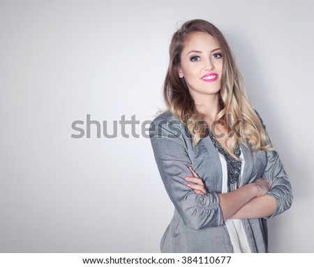 Young attractive friendly smiling professional business woman with arms crossed - stock photo