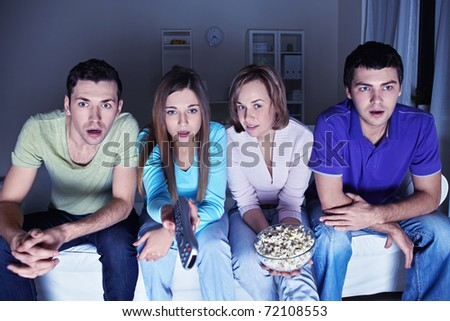 Young attractive friends watch in amazement at the TV - stock photo