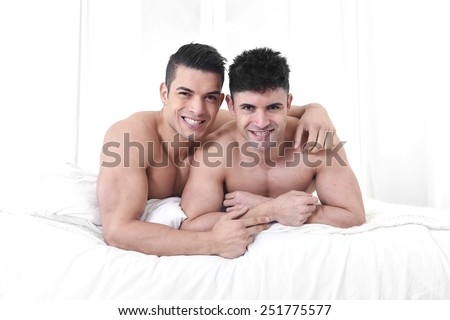 young attractive gay men couple lying on bed together in bedroom smiling happy in love with naked torso in homosexual relationship concept - stock photo