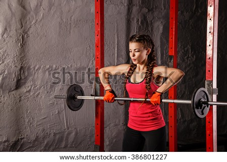 Young attractive girl athlete doing exercises with a barbell. Sport Club. Fitness club. Healthy lifestyle concept. - stock photo