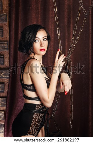 Young attractive girl in bra and lace underwear. Girl hands handcuffed with chains. The concept of BDSM and bondage. - stock photo
