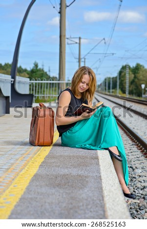 Young attractive girl in long skirt sitting on the train station and reading a book - stock photo