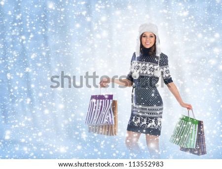 Young attractive girl in native scandinavian clothes makes shopping over winter background - stock photo