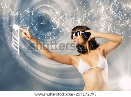 Young attractive girl in white bikini touching icon - stock photo