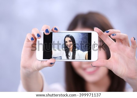 Young attractive girl making photo by her self with mobile phone on grey background, close up - stock photo