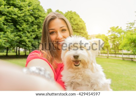 Young attractive girl taking a selfie with her dog - stock photo