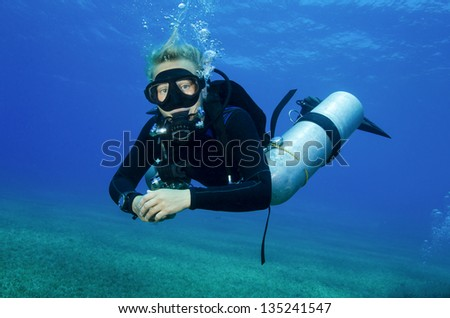 young attractive girl, tech scuba dives in clear blue water - stock photo