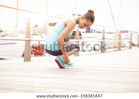 young attractive girl tying her running shoes before a morning exercise - stock photo