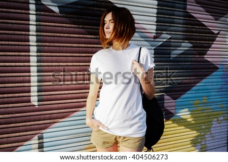 young attractive girl with a backpack wearing a white t-shirt standing on a graffiti wall background  - stock photo